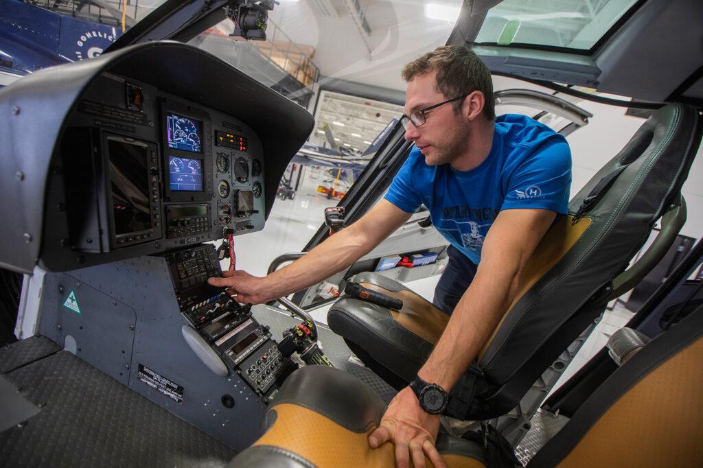 Mathieu Lebel penché au-dessus des instruments de la cabine d'un hélicoptère pendant qu'il effectue la maintenance.