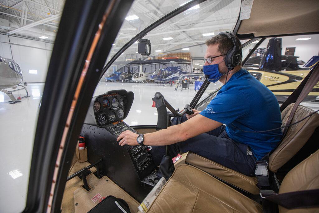 Mathieu Lebel aux commandes d'un hélicoptère dans le hangar du Centre de maintenance Capitale Hélicoptère.