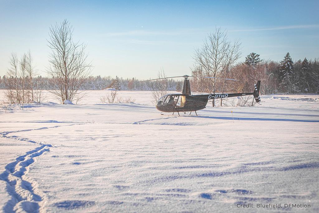Hélicoptère Robinson RH44 ayant atterri dans un champ enneigé.