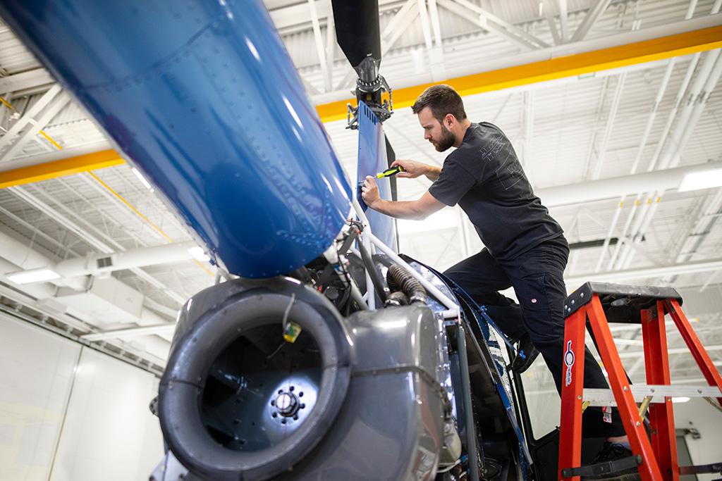 Employé du Centre de Maintenance de Capitale Hélicoptère sur un escabeau en train de réparer un hélicoptère.