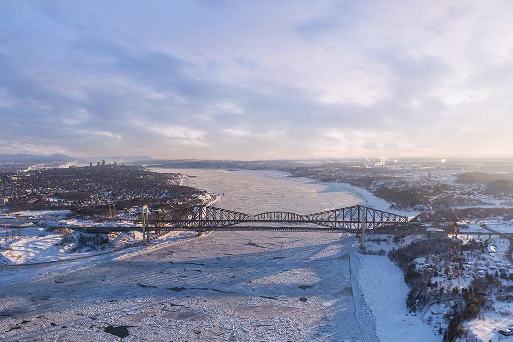 Vue aérienne d'un paysage hivernal du pont de Québec surplombant le fleuve Saint-Laurent gelé.
