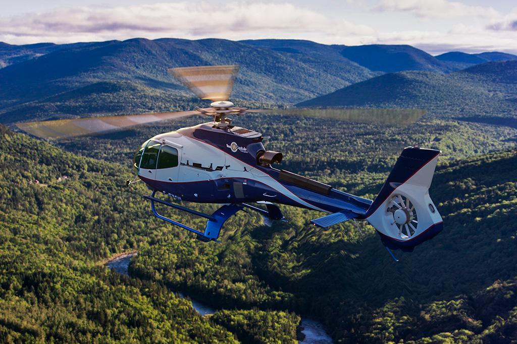 Hélicoptère volant au-dessus d'une rivière entourée de montagnes couvertes de forêts.