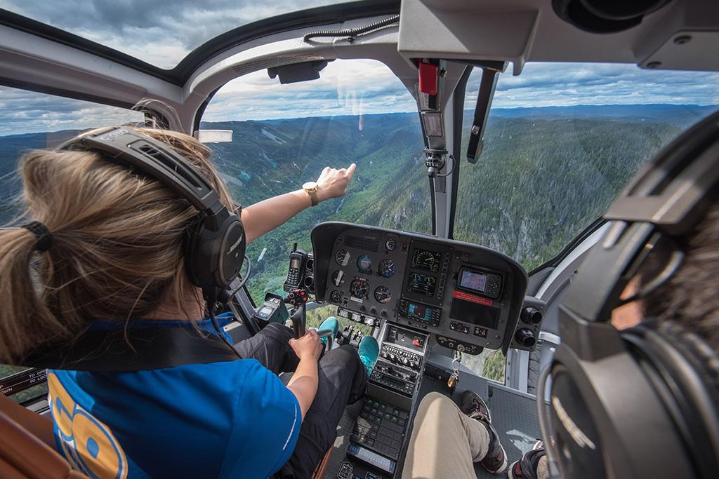 Femme pilote d'hélicoptère pointant et expliquant les attraits à ses passagers.