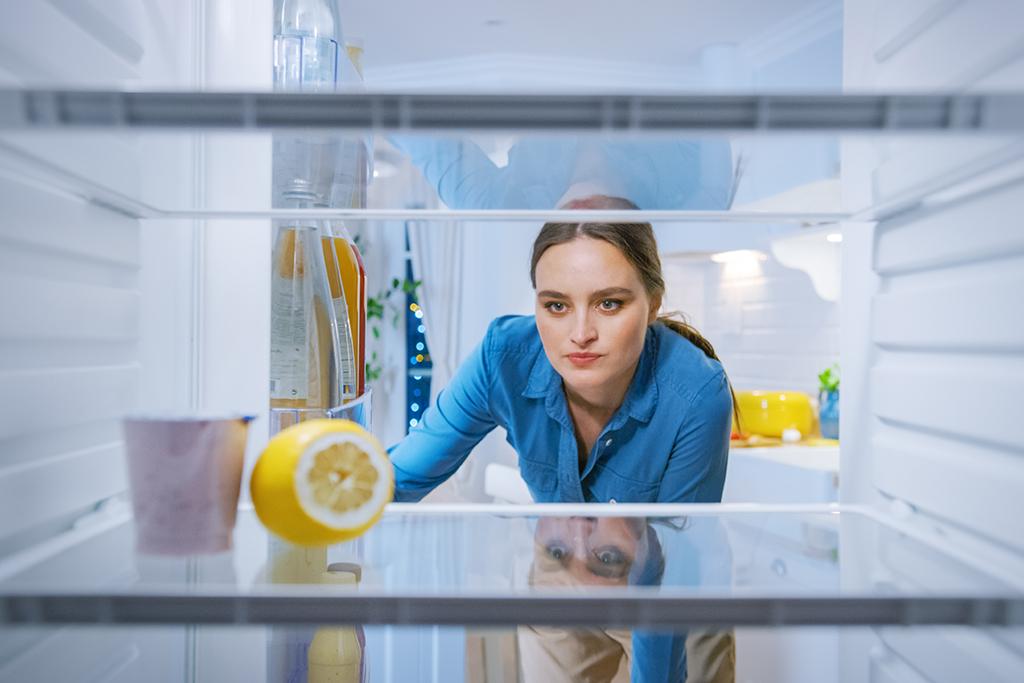 Jeune femme qui regarde à l'intérieur de son réfrigérateur vide.