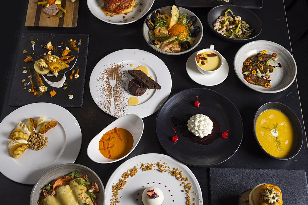 Panoplie de plats à cuisiner à la maison du Resto-Bar Le Commandant disposée élégamment dans de belles assiettes.