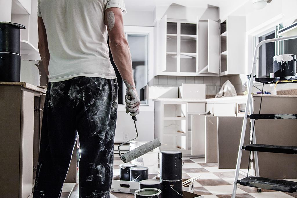 Homme, rouleau de peinture à la main, prêt à refaire la cuisine.