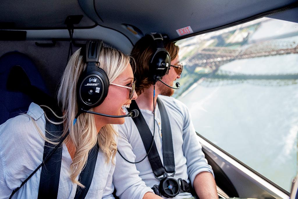 Jeune couple à bord d'un hélicoptère de GoHelico en train de regarder le pont de Québec au loin.