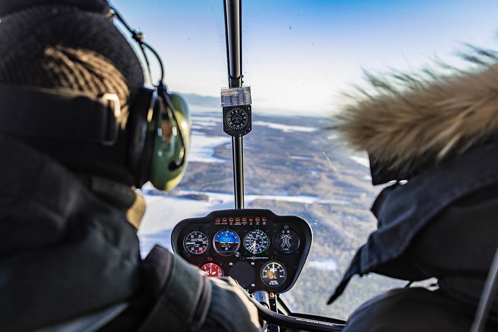 Pilote d'hélicoptère et son passager en vol dans le cockpit en hiver.
