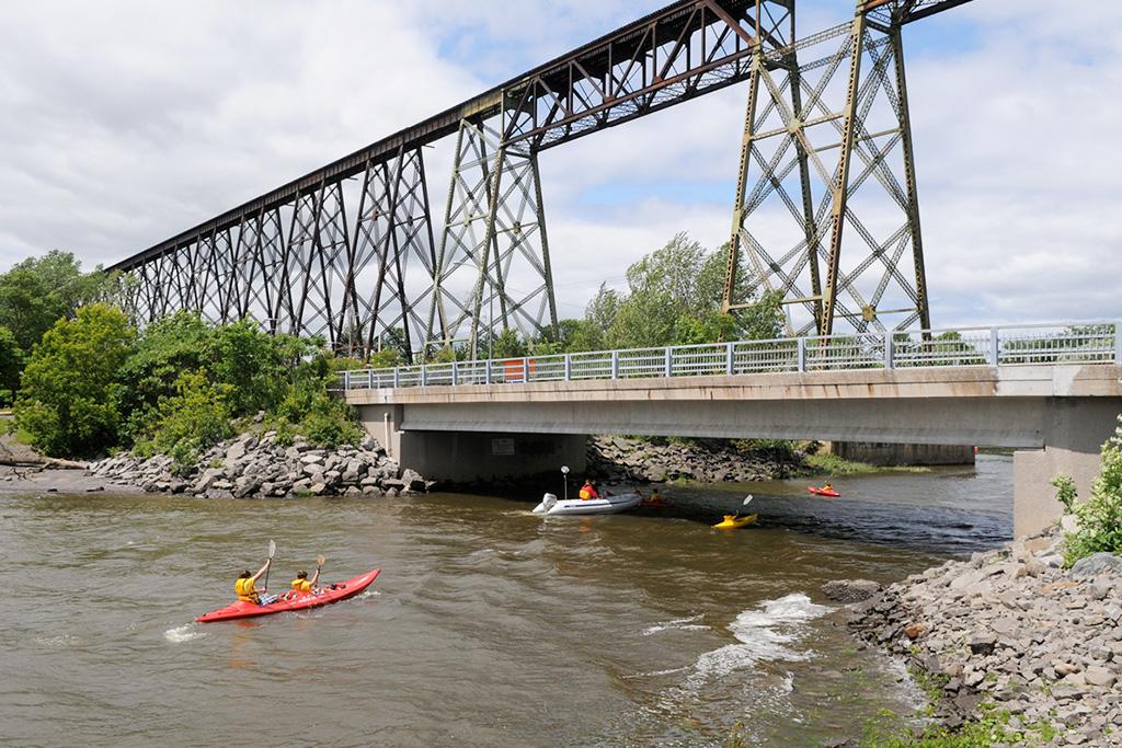 Kayakistes passant sous un pont avant d'arriver au Tracel de Cap-Rouge.