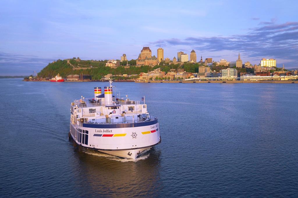 Le bateau Louis Jolliet navigant sur le fleuve Saint-Laurent en s'éloignant de la ville de Québec.
