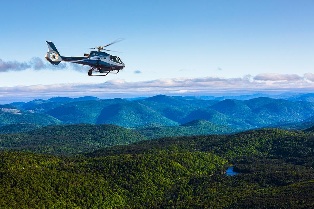 Vol pour apprendre à piloter un hélicoptère au-dessus de montagnes couvertes de forêts.