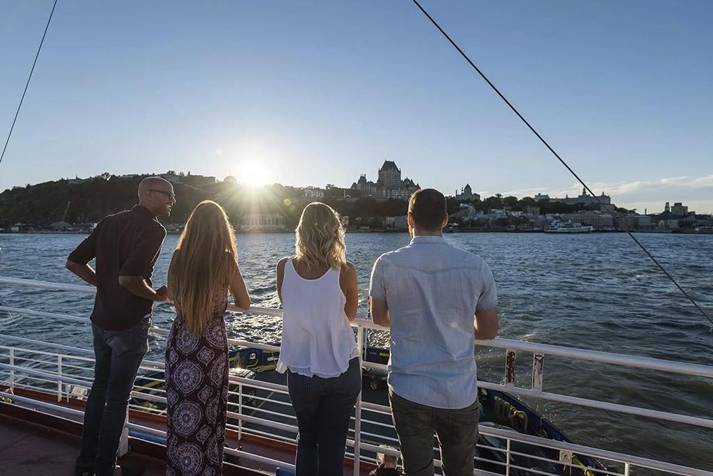 Quatre personnes sur la traverse Québec-Lévis regardant la ville de Québec au loin au coucher de soleil.