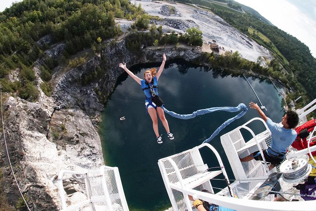 Femme en train de faire un saut de bungee dans une carrière vers l'eau. Titre : Activités