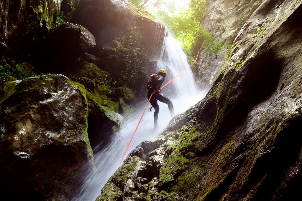 Une personne en quête d'activités adrénaline au Québec qui remonte une rivière lors d'une excursion de canyonisme.