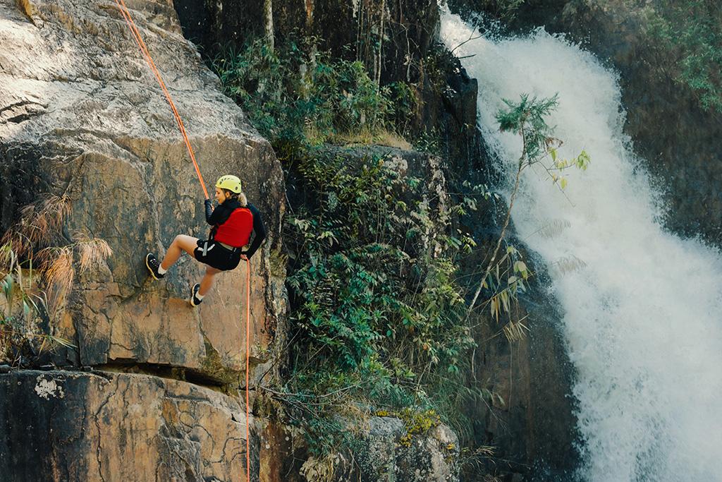 Grimpeur en rappel sur une paroi rocheuse près d'une chute.