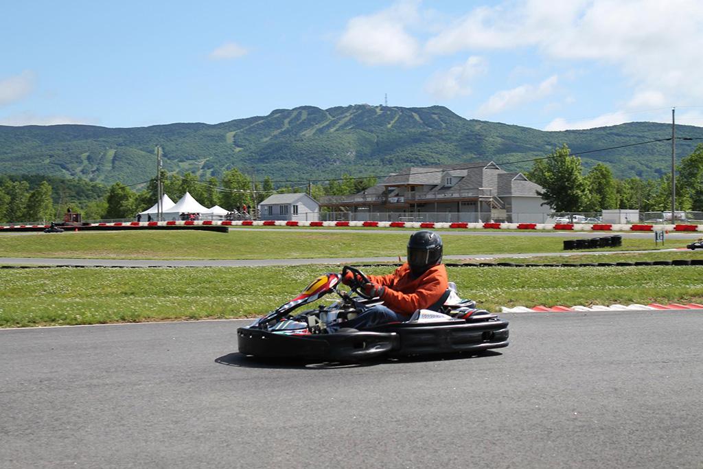 Pilote au volant de son kart sur la piste de course.