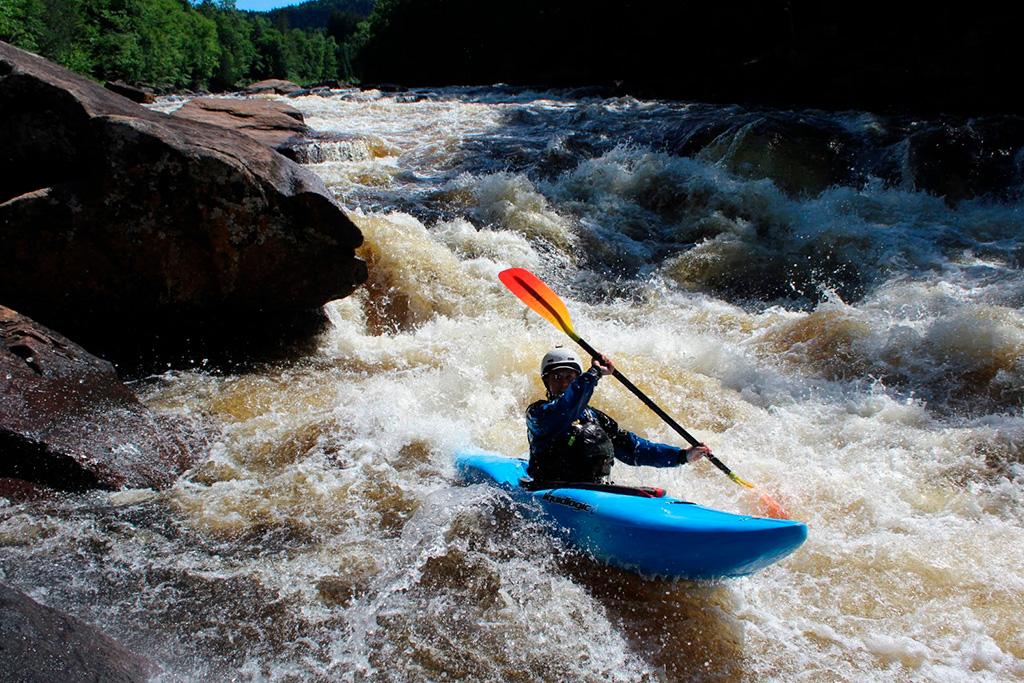 Activités adrénaline au Québec : kayakiste d'eau vive dans un kayak bleu pagayant dans les remous d'une rivière.