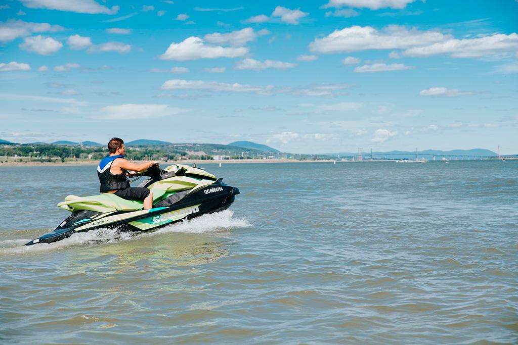 Un homme sur sa motomarine navigue sur l'eau calme.