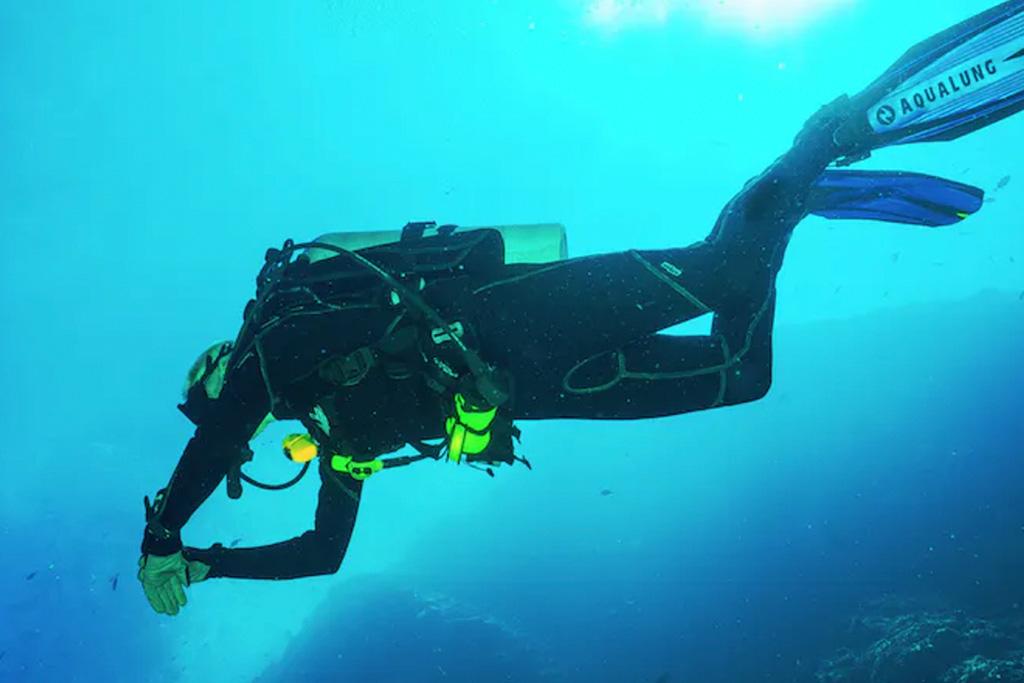 Un adepte de plongée sous-marine dans l'eau, tout équipé et habillé d'un wetsuit long.