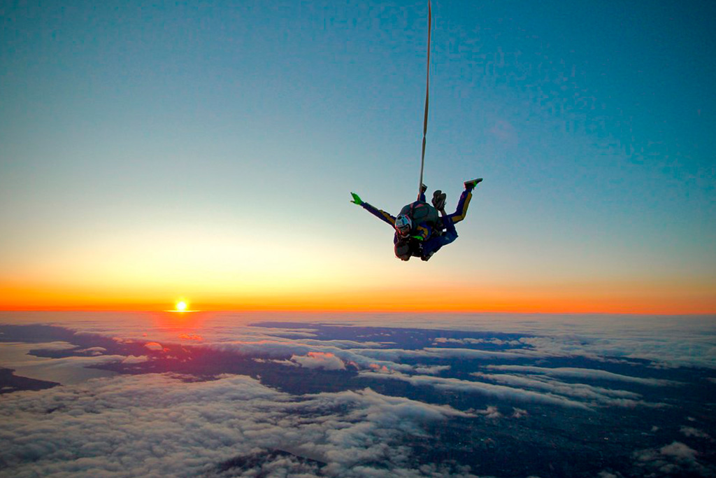 Parachutistes en tandem au-dessus des nuages au coucher du soleil.