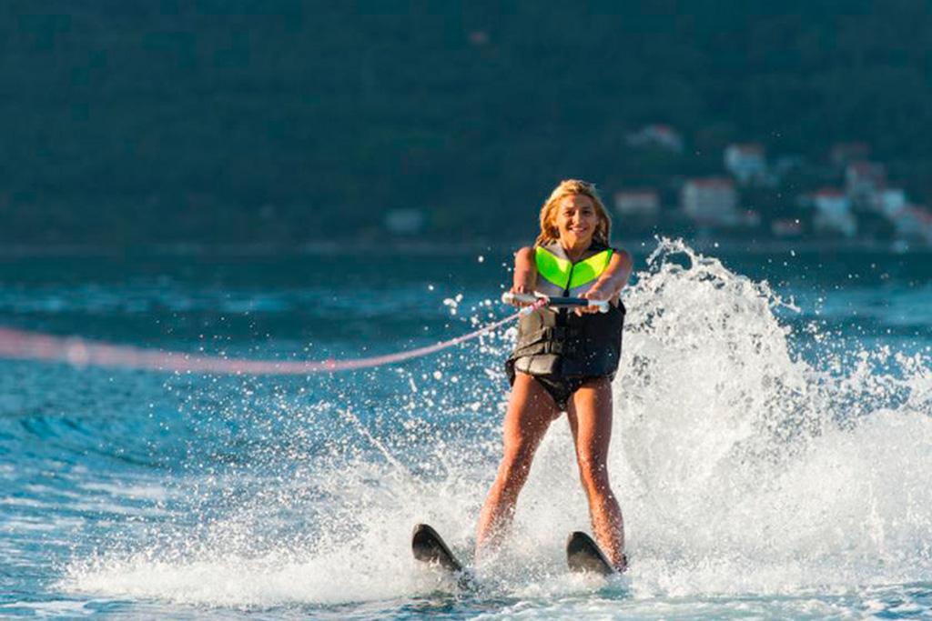 Activités adrénaline au Québec : une femme vêtue d'une veste de sauvetage fait du ski nautique.