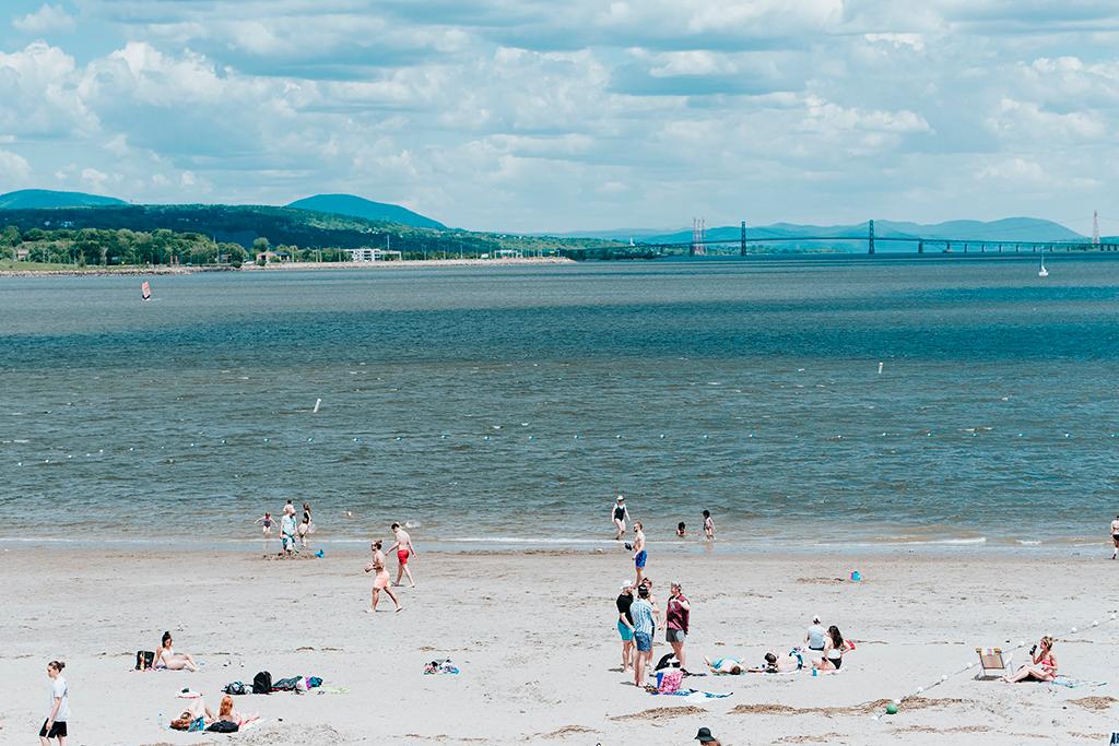 Gens sur la plage de la Baie de Beauport Sun Life et vue au loin du fleuve Saint-Laurent et du pont de l'île d'Orléans.