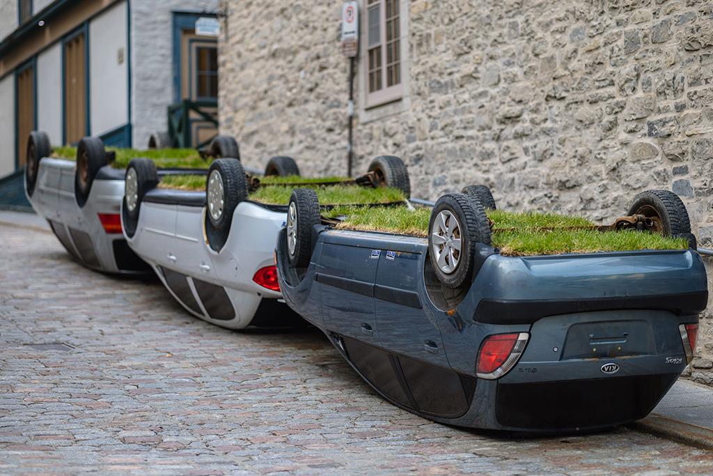 Les Passages insolites : 3 voitures garées et renversées sur le toit, remplies de terre et recouvertes de pelouse.