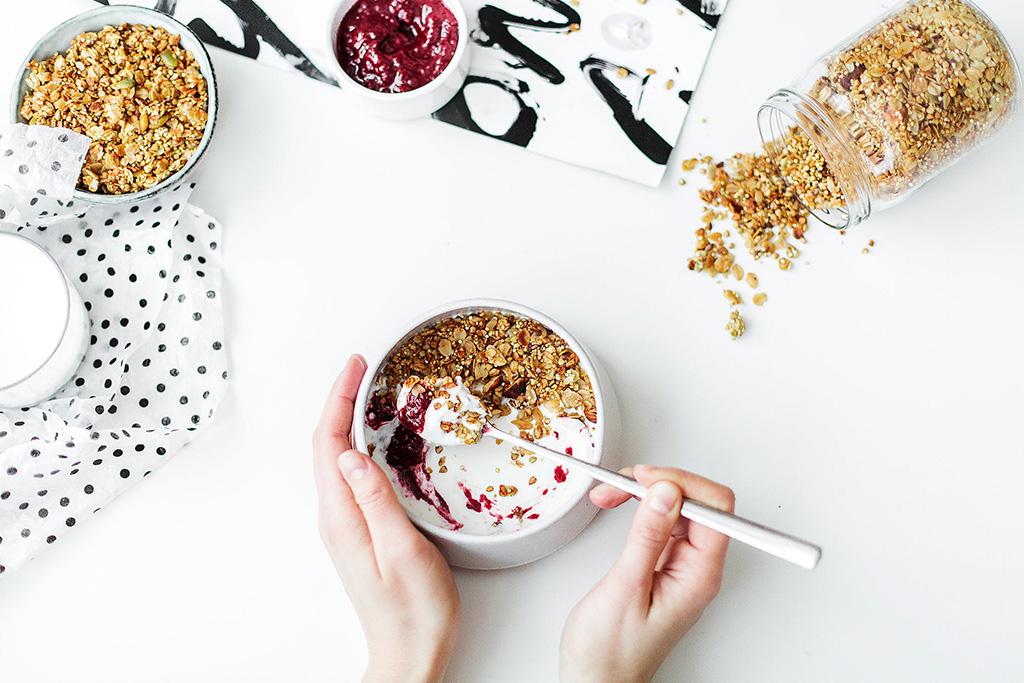 L'importance du déjeuner : un bol de yogourt avec confiture, céréales et noix.