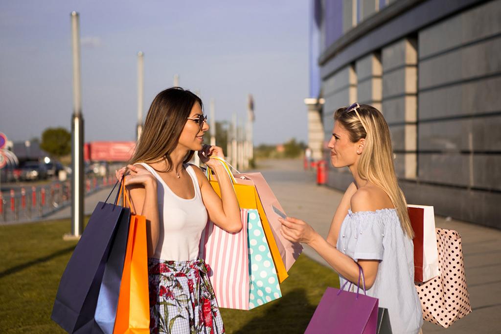 Quoi faire à Québec cet été : du magasinage comme ces 2 femmes les bras chargés de sacs après une journée à magasiner.