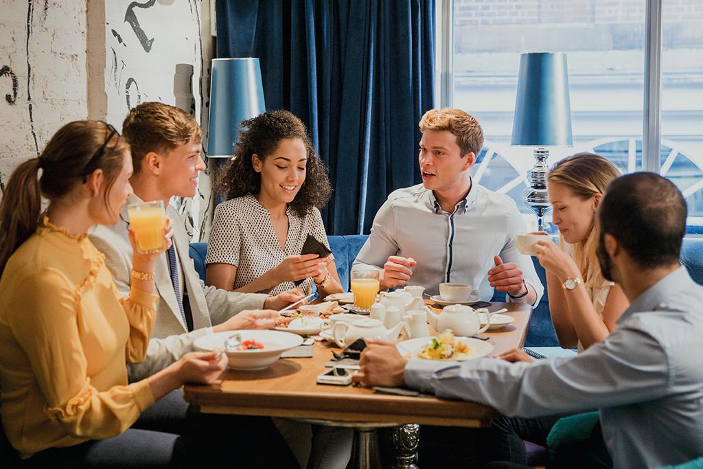 Six jeunes professionnels autour d'une table dans un restaurant pour le déjeuner.
