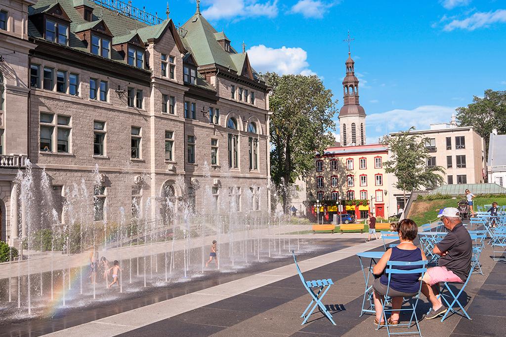 Un couple assit à la place éphémère des Jardins de l'Hôtel-de-Ville et regardant les enfants dans la fontaine.