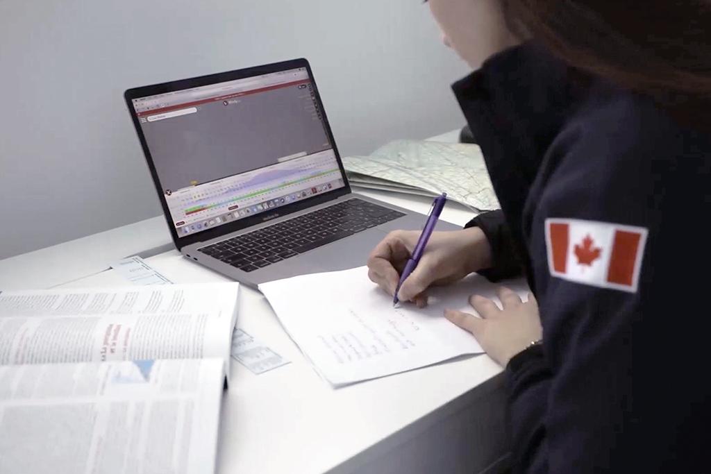 Étudiante de l'école de pilotage d'hélicoptère devant son ordinateur et ses livres pendant qu'elle prend des notes.