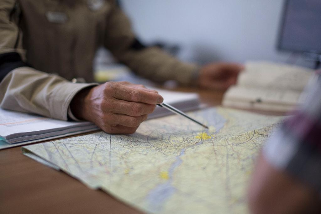 Un instructeur de l'école de pilotage d'hélicoptère pointe sur une carte pendant un briefing avec un étudiant.