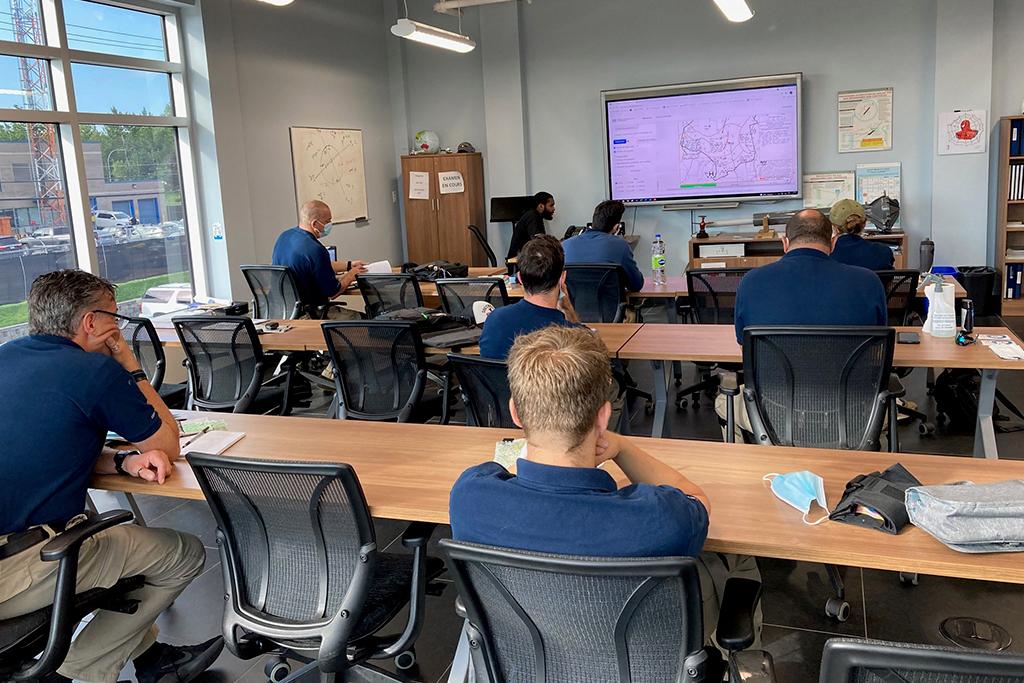 Sept étudiants de l'École de pilotage Capitale Hélicoptère assis en classe pendant un cours théorique.