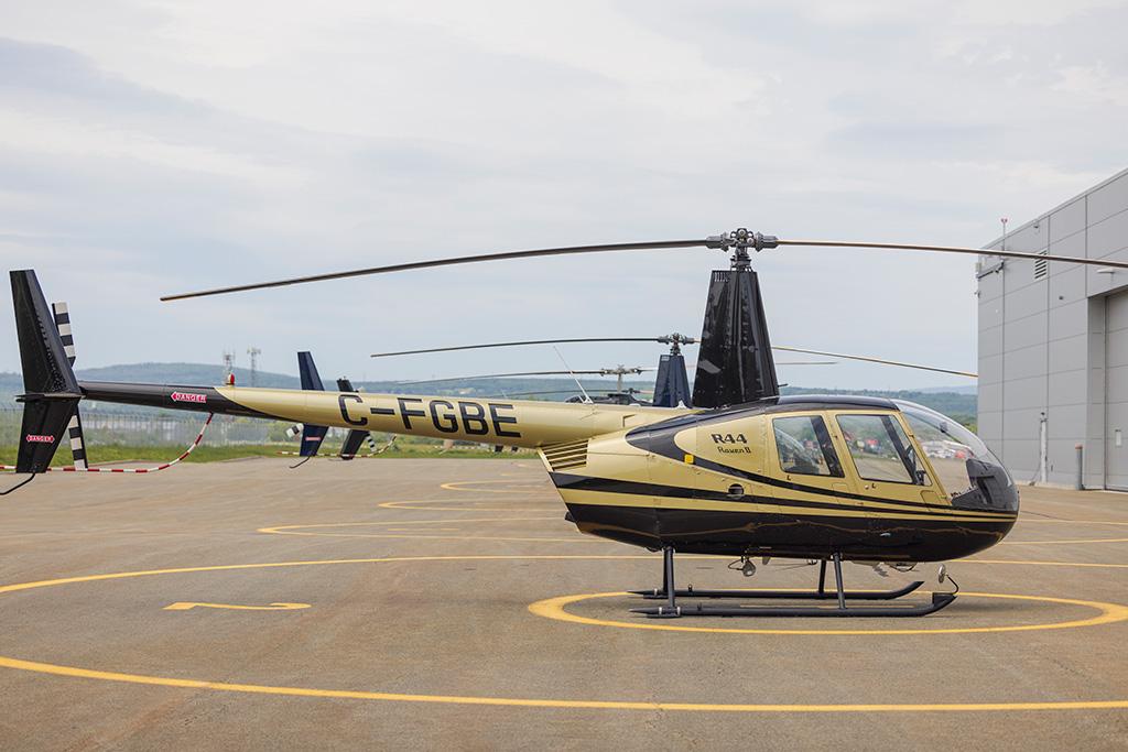 Vue de profil de l'hélicoptère Robinson R44 appartenant au pilote privé Joël Mailloux, au Complexe Capitale Hélicoptère.