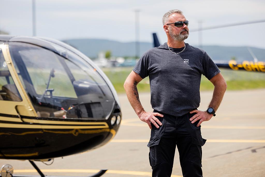 Joël Mailloux et son hélicoptère R44, les mains sur les hanches et regardant vers l'École de pilotage Capitale Hélicoptère.