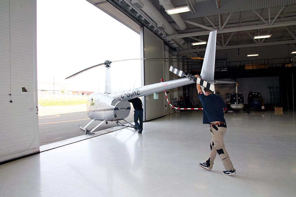 La sortie de l'hélicoptère du hangar par l'instructeur positionné au niveau du fuselage et son étudiant à la queue.